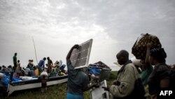 Des personnes embarquent dans des pirogues sur le lac Albert pour fuir les violences en Itrui vers l'Ouganda à Tchomia, le 5 mars 2018.