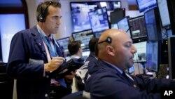 8일 미국 뉴욕증권거래소에서 증권업자들이 전광판을 보고 있다.