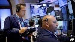 交易员在纽约证券交易所交易大厅内工作。(2015年7月8日,美联社)