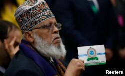 Imam Sheikh Sa'ad Musse Roble of Minneapolis holds up a card from the World Peace Organization as he listens to President Barack Obama during his speech before the White House Summit on Countering Violent Extremism, Feb. 18, 2015.