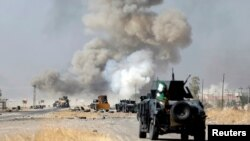FILE - An improvised explosive device planted by Islamic State fighters explodes in front of Iraqi special forces vehicles in Bartella, east of Mosul, Iraq, Oct. 20, 2016.