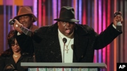 The Notorious BIG, qui a remporté le prix de l'artiste rap et du single rap de l'année, récupère ses prix sur le podium lors des Billboard Music Awards annuels à New York, le 6 décembre 1995. (Photo AP / Mark Lennihan, dossier)