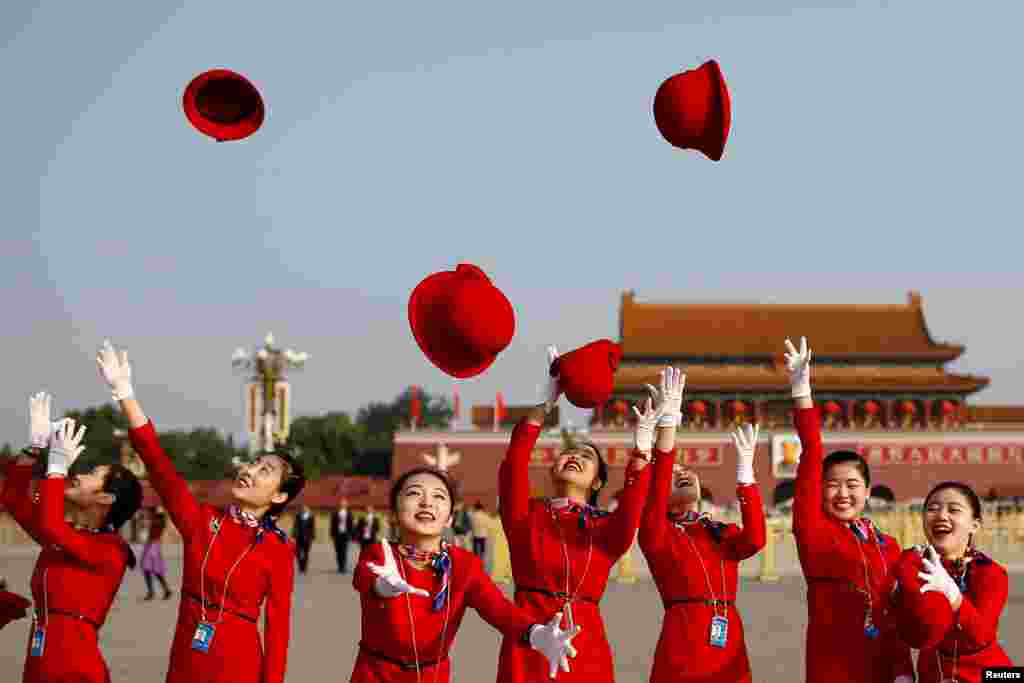 Ushers throw their hats in the air as they pose for photographers at the Tiananmen Square before the closing session of the 19th National Congress of the Communist Party of China, in Beijing.