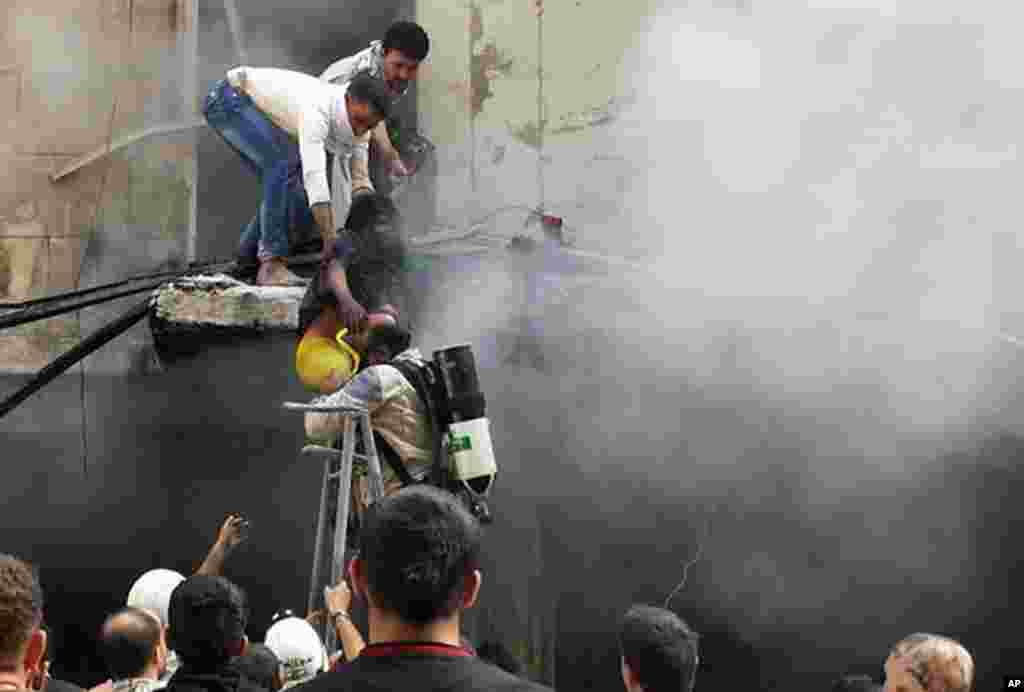 This photo provided by the activist group Syrian Observatory for Human Rights shows men helping a survivor out of a damaged building following a Syrian government airstrike in Karm al-Jabal, Aleppo, Syria, June 26, 2014.