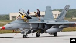 FILE - An Australian fighter jet is readied for a training mission at Andersen Air Force Base on the U.S. island of Guam, Feb. 7, 2013. Australia announced Friday that it would recall its fighter jets from Iraq and Syria.