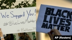 "From left, a Baltimore police supporter holds a ""Blue Lives Matter"" poster, May 30, 2015; and a man holds a sign saying ""Black Lives Matter"" during a protest of shootings by police by the White House in Washington, July 8, 2016."
