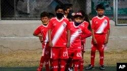 Niños ecuatorianos asisten a la academia de fútbol Jaime Páez al comenzar el año académico el 1 de septiembre de 2021 en Quito.