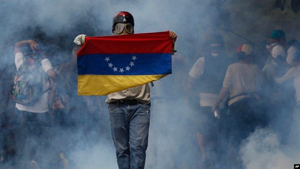 Un manifestante antigubernamental camina en medio de los gases lacrimógenos durante un enfrentamiento con las fuerzas de seguridad, el miércoles en Caracas.