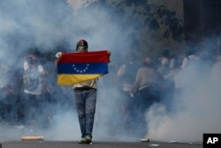 ຜູ້ປະທ້ວງຕໍ່ຕ້ານລັດຖະບານ ຄົນນຶ່ງ ຖືທຸກຊາດ ຂອງເວເນຊູເອລາ ໃນລະຫວ່າງ ການປະທະກັນ ກັບກຳລັກຮັກສາຄວາມປອດໄພ ໃນນະຄອນຫຼວງ Caracas, Venezuela, ວັນທີ 19 ເມສາ 2017.