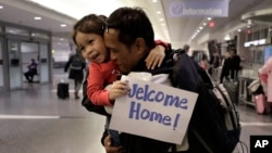 Thy Chea, of Lowell, Mass., center right, originally of Cambodia, hugs his daughter on his arrival at Boston's Logan Airport, Wednesday, Feb. 26, 2020, after getting his green card reinstated last year.