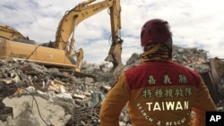 FILE - A member of rescue teams stands by as heavy excavation machinery continues to dig through the rubble of a collapsed building complex in Tainan, Taiwan, Thursday, Feb. 11, 2016.