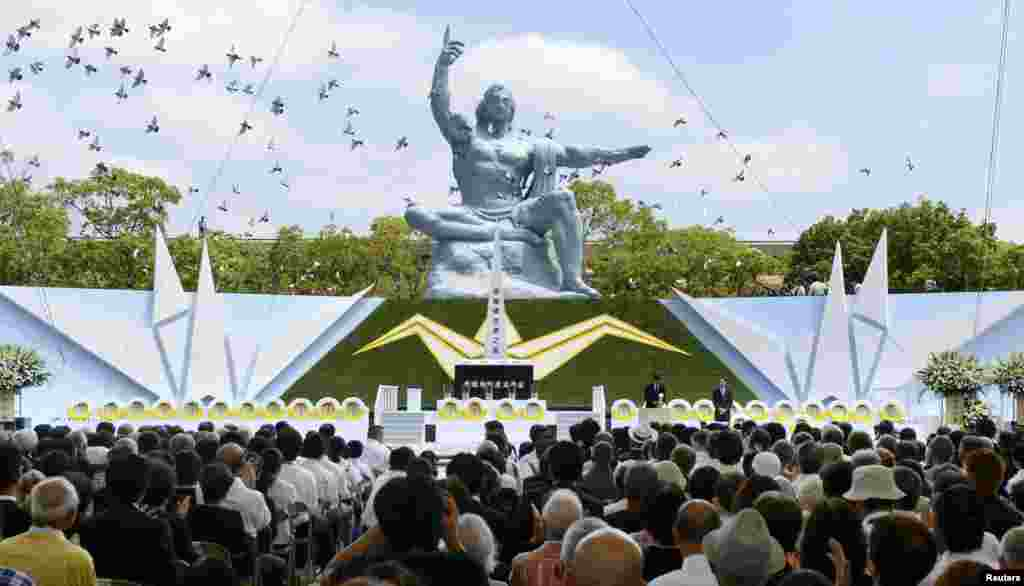 Doves fly near the Peace Statue in Nagasaki's Peace Park during a ceremony commemorating the 68th anniversary of the atomic bombing of the city, August 9, 2013. (Reuters/Kyodo)