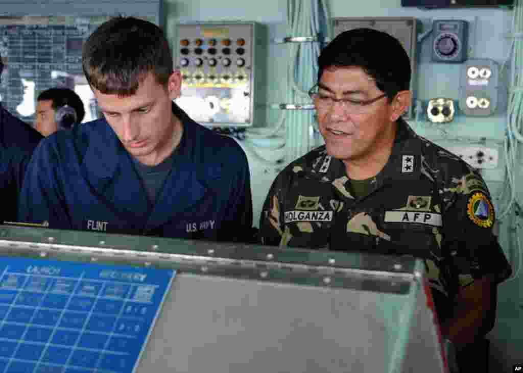 菲律賓蘇祿灣 (2012年4月22日) 美軍兩棲船塢艦丹佛號水手弗林特向登船造訪的菲律賓武裝部隊後勤司令霍爾甘薩展示如何操舵。