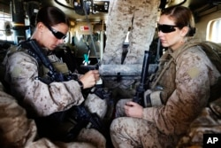 FILE - U.S. Marine and Female Engagement Team leader Sgt. Sheena Adams (L) and H.N. Shannon Crowley from First Battalion, Eighth Marines sit in an armored vehicle before heading out on an operation from their base at Musa Qala in southern Afghanistan's Helmand province.