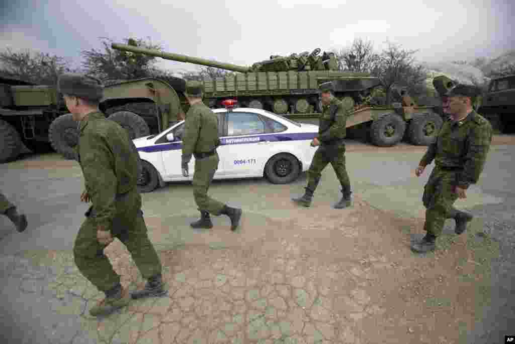 Russian police cars drive and Ukrainian soldiers walk behind Ukrainian tanks at Perevalnoe, outside Simferopol, Crimea, March 26, 2014.