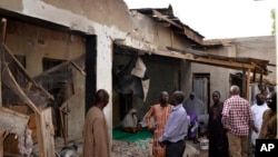 FILE - People inspect houses damaged in Saturday's rocket-propelled grenades by Islamic extremist in Maiduguri, Nigeria, May 31, 2015.