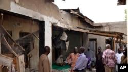 尼日利亚迈杜古里市居民正在查看被伊斯兰国武装炸坏的房屋(2015年5月31日)