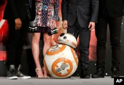 "BB-8 droid poses with actors and director during a press conference for their latest film ""Star Wars: The Force Awakens"" at a hotel in Urayasu, near Tokyo, Dec. 11, 2015."