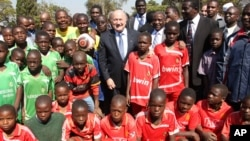 FIFA: Fifa President Sepp Blatter, centre, poses for a photo with schoolchildren during his visit to the Zimbabwe Football Association Village in Mount Hampden about 40 kilometres west of Harare, Monday, July, 4, 2011. (AP Photo/Tsvangirayi Mukwazhi)