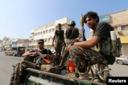 FILE - Houthi militants patrol a street where pro-Houthi protesters demonstrated against the Saudi-led coalition in Hodeida, Yemen.