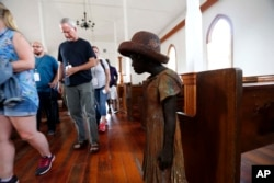 "FILE - In this July 14, 2017 file photo, visitors file past the sculpture of a slave girl, one out of 40 statues spread about the grounds, titled, ""Children of Whitney,"" by Woodrow Nash, inside the Antioch Baptist Church"