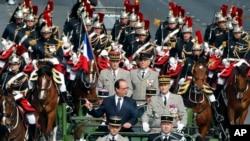 在巴士底日阅兵式上,法国总统奥朗德站在指挥车上阅兵。(2014年7月14日)