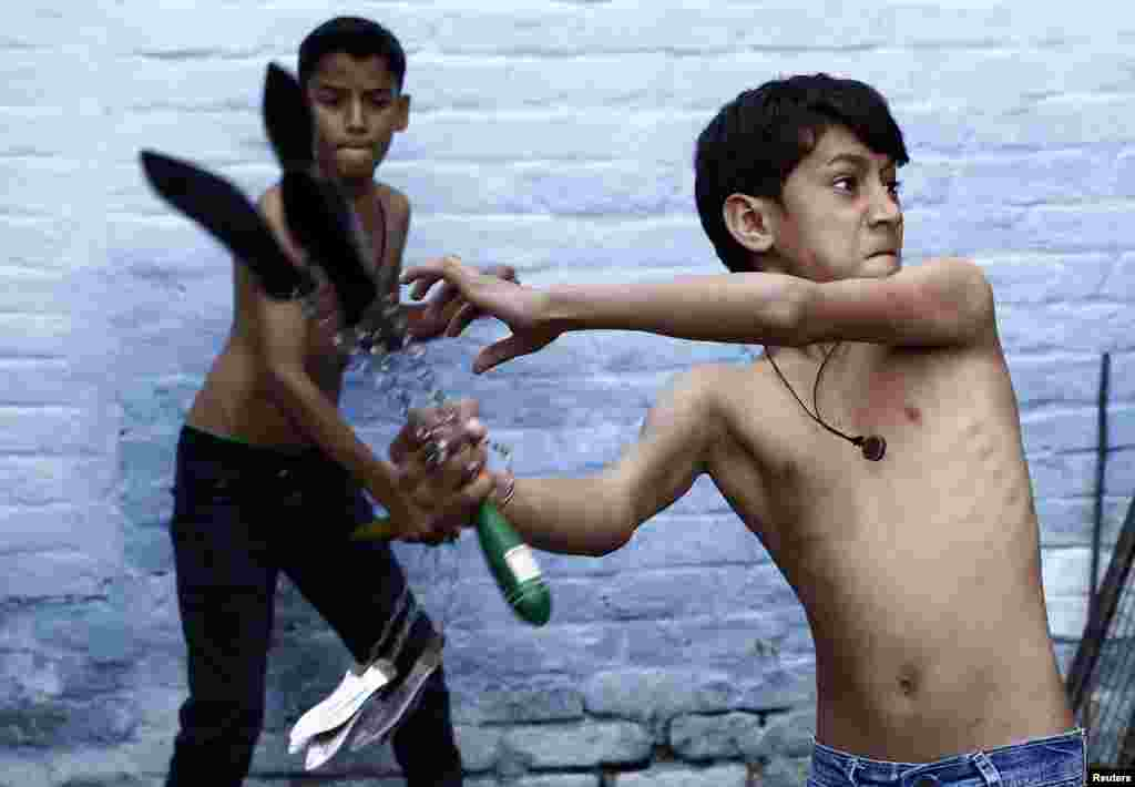 Shia Muslim boys flagellate themselves during a Muharram procession ahead of Ashura in Amroha, in the northern Indian state of Uttar Pradesh. Ashura, which falls on the 10th day of the Islamic month of Muharram, commemorates the death of Imam Hussein, grandson of Prophet Mohammad, who was killed in the 7th century battle of Kerbala.