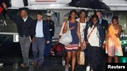 El presidente Barack Obama (izquierda) y su familia se preparan para abordar el avión presidencial para regresar a Washington desde Massachusetts.