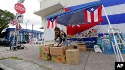 Warga di Miami, Florida mengumpulkan makanan yang akan disumbangkan ke Puerto Rico, Rabu (27/9).