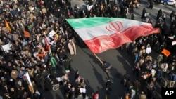 En esta foto proporcionada por la agencia de noticias Tasnim, un manifestante ondea una enorme bandera iraní durante las protestas en Mashad, Iran, el jueves 4 de enero.