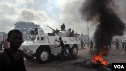 Kendaraan pasukan keamanan PBB melewati para suporter Alassane Ouattara yang berdemo di Abidjan.