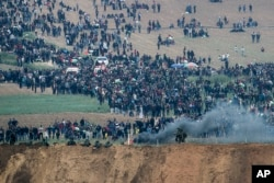 Israeli soldiers stand as Palestinian protesters gather on the Israel Gaza border, Friday, March 30, 2018.