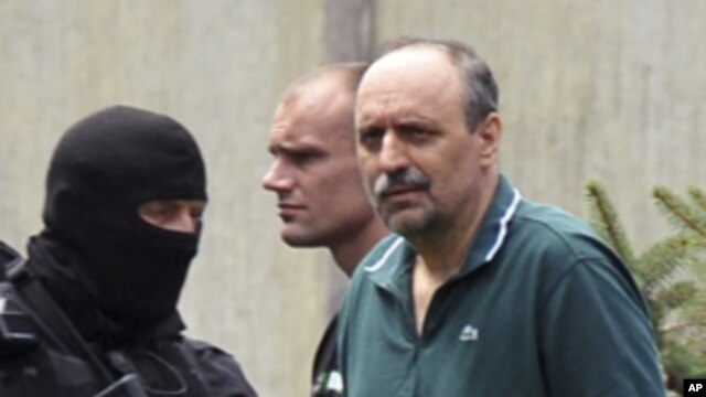 Serbian police officers escort Goran Hadzic (R), after he visited his terminally ill mother in Novi Sad July 22, 2011. Serbia on Friday extradited Goran Hadzic, the last ethnic Serb wanted by the International Criminal Court in The Hague, in a symbolic mo