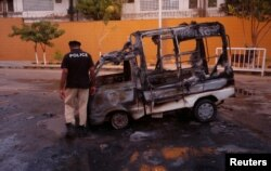 A policeman inspects a vehicle burned by Mutahida Qaumi Movement (MQM) political party protesters, in Karachi, Pakistan, Aug. 22, 2016.