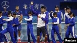 "Jo-Wilfried Tsonga (belakang) menonton Novak Djokovic menari ""Gangnam Style"" bersama para penjaga bola setelah memenangkan Turnamen Cina Terbuka. (Reuters/Jason Lee)"