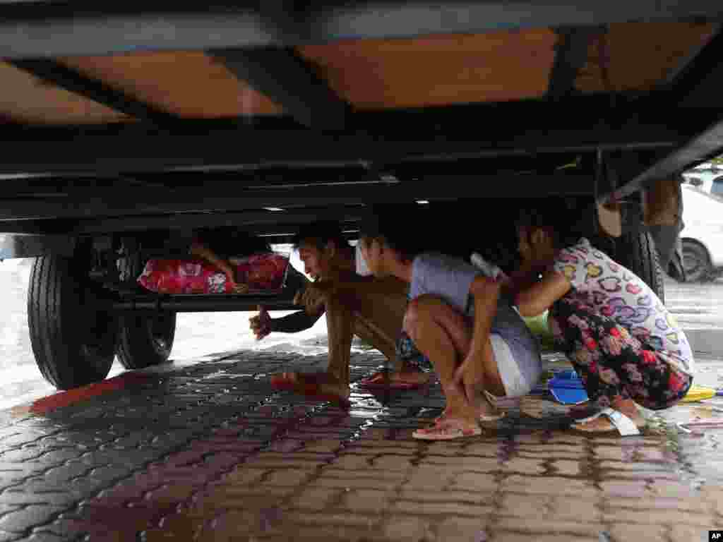Filipinos take cover from the rain underneath a container van as Tropical Storm Linfa enhanced the southwest monsoon in Manila, the Philippines.