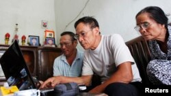 FILE - Veteran Le Dung (C) reads articles on the Internet with Dang Van Dat (L) and Tran Thi Thanh Kiem (R) at his house in Van Giang district, outside Hanoi, Vietnam.
