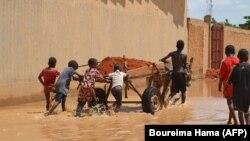 Des enfants transportent de la latérite sur un chariot pour construire des barrages afin d'arrêter les eaux du fleuve Niger à Niamey le 3 septembre 2019.
