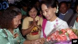 缅甸反对派领导人昂山素季(右)2015年6月10日离开仰光前往北京访问在仰光国际机场接受支持者献花