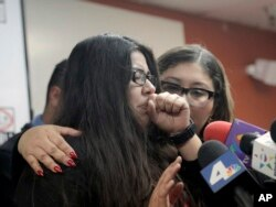 Marlene Mosqueda, left, who's father was deported Feb. 10, 2017, is comforted at a news conference by her attorney Karla Navarrette at The Coalition for Humane Immigrant Rights of Los Angeles.