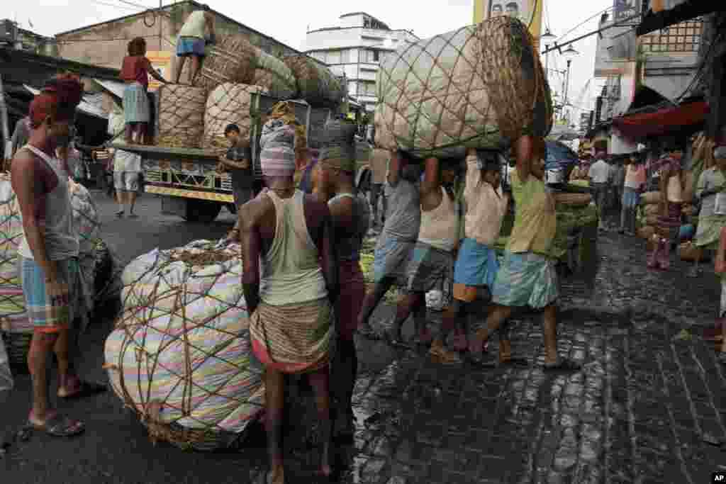 Công nhân Ấn Độ với các bao rau cải khổng lồ tại chợ bán sỉ thực phẩm ở thành phố Kolkata.