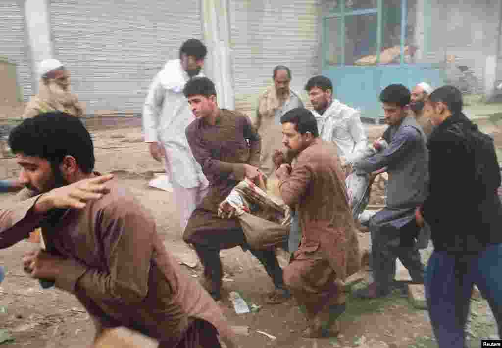 Afghan men carry an injured man after a blast in Jalalabad.