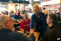 Sen. Kirsten Gillibrand, D-N.Y. greets patrons at Stomping Grounds Cafe in Ames, Iowa, Jan. 19, 2019.