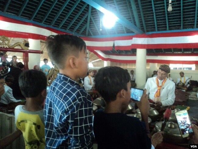 Sejumlah anak merekam video dengan gawai saat prosesi tabuhan gamelan sekaten di Masjid Agung Solo. (Foto: VOA/Nurhadi)