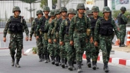 Soldiers walk outside the National Anti-Corruption Commission office in Nonthaburi province, on the outskirts of Bangkok, Feb. 27, 2014.