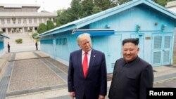 Prezidan Donald Trump ki t ap rankontre ak lidè Kore di Nò a, kim Jong Un, nan vilaj Panmunjom, Kore di Sid, nan zòn demilitarize a ki separe 2 Kore yo, nan dat 30 jen 2019. (Foto: Kevin Lamarque/Dosye Achiv).