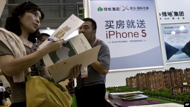 A real estate agent explains property development details to a woman during the China Property and Investment Show in Beijing, September 21, 2012.