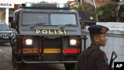 ຕຳຫຼວດຢືນຍາມໃກ້ໆລົດຫຸ້ມເກາະຄັນນຶ່ງນອກປ້ອມຕຳຫຼວດ ຫຼັງຈາກເກີດເຫດລະເບີດ ທີ່ເມືອງ Cirebon ເຂດພາກຕາເວັນຕົກ ຂອງເກາະ Java (15 ເມສາ 2011)