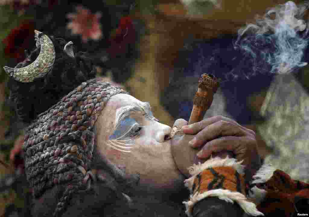 Seorang pria berpakaian sebagai dewa Hindu, Shiva, merokok dalam festival keagamaan Hindu yang dikenal dengan festival Shyam Baba di Ajmer, di negara bagian Rajasthan, India.