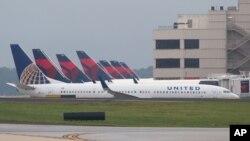 FILE - A United Airlines plane passes Delta planes parked at Atlanta's Hartsfield International Airport in Atlanta, Ga., Aug. 8, 2016.